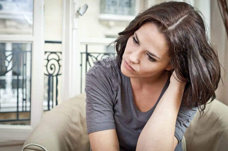Brünette Frau, die zu Hause sitzt, sieht nachdenklich aus