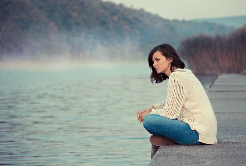 Das Mädchen sitzt am See