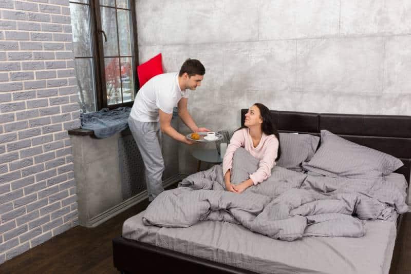 Der hübsche Mann brachte das Frühstück ins Bett, während seine Freundin aufwachte