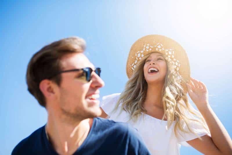 lächelnde Frau, die Hut trägt, der hinter glücklichem Mann steht