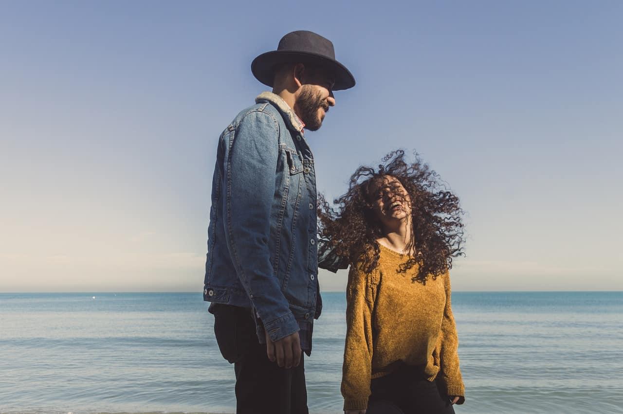 Ein Mann mit Hut und einer lächelnden Frau am Strand