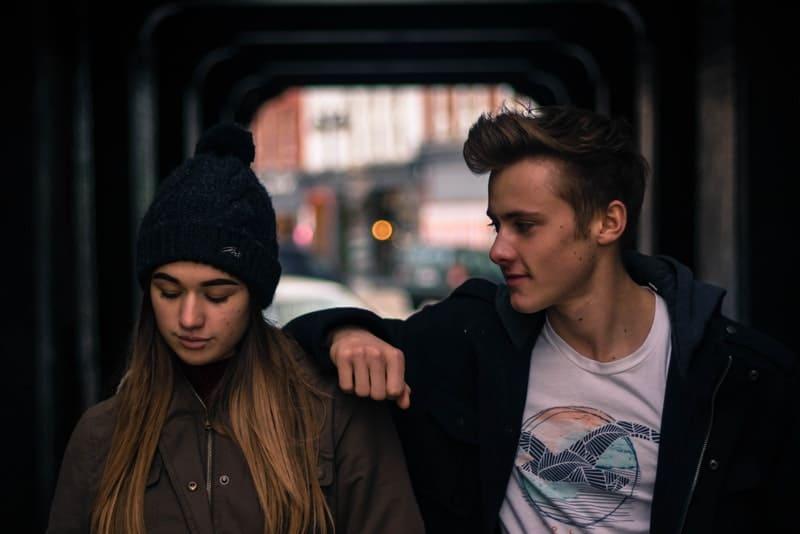 Ein junger Mann und seine Freundin gehen durch eine Unterführung