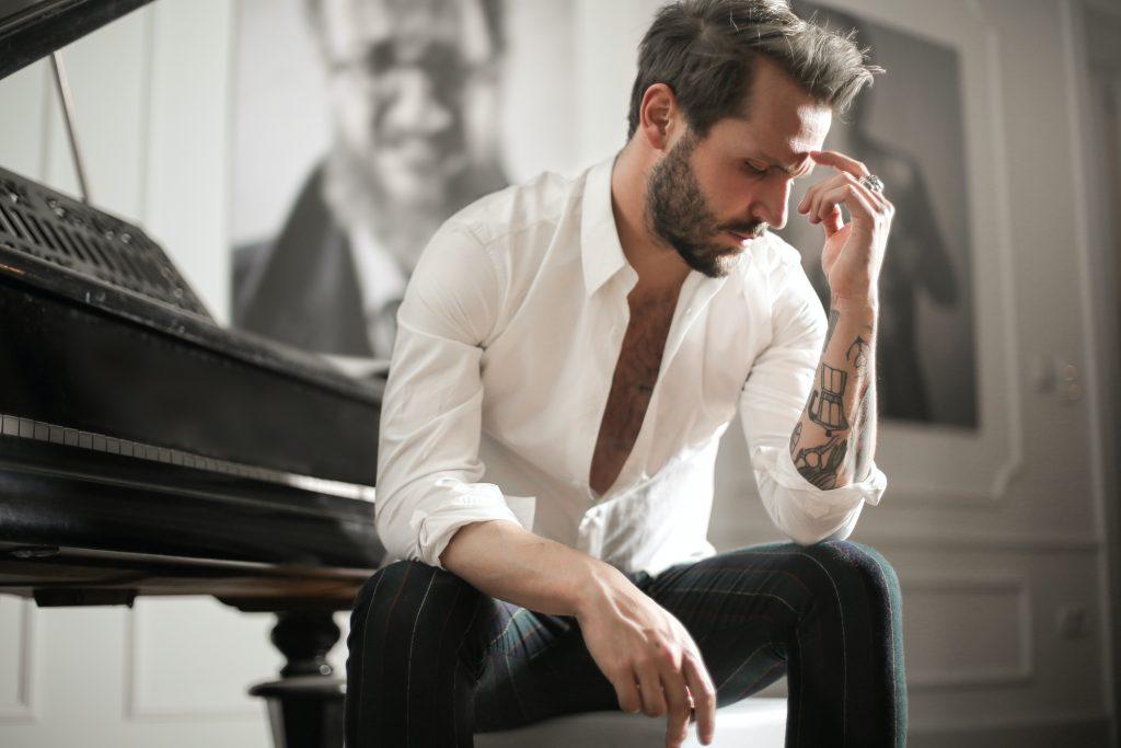Ein trauriger Mann mit einem Tattoo auf dem Arm sitzt neben einem Klavier