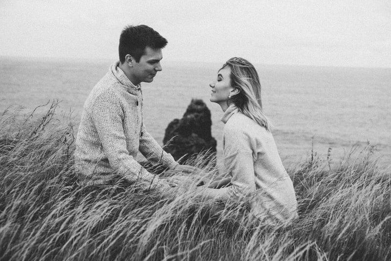 Ein verliebtes Paar sitzt im Gras über dem Meer