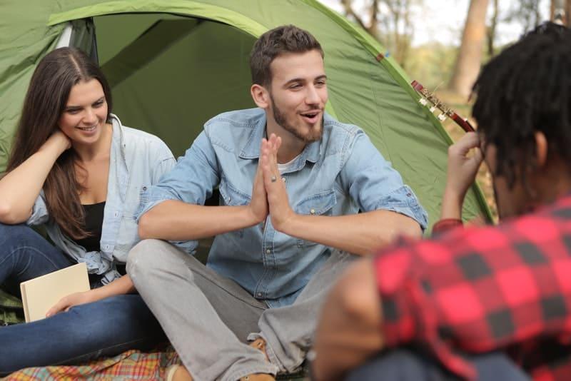 Eine Gruppe von Freunden sitzt vor dem Zelt und redet