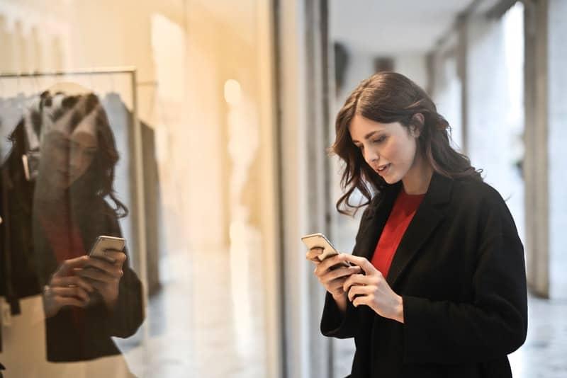 Eine junge Frau vor einem Schaufenster schaut auf ihr Handy