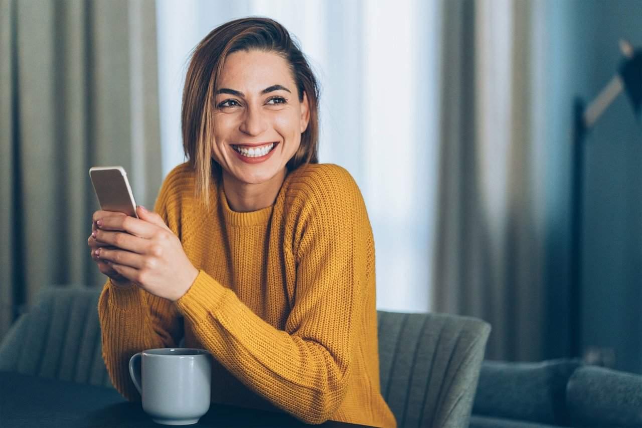 Eine lächelnde Frau sitzt an einem Tisch und hält ein Telefon in der Hand