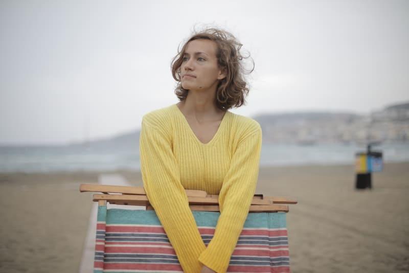 Eine traurige Frau hält einen Klappstuhl in den Händen und schaut in die Ferne