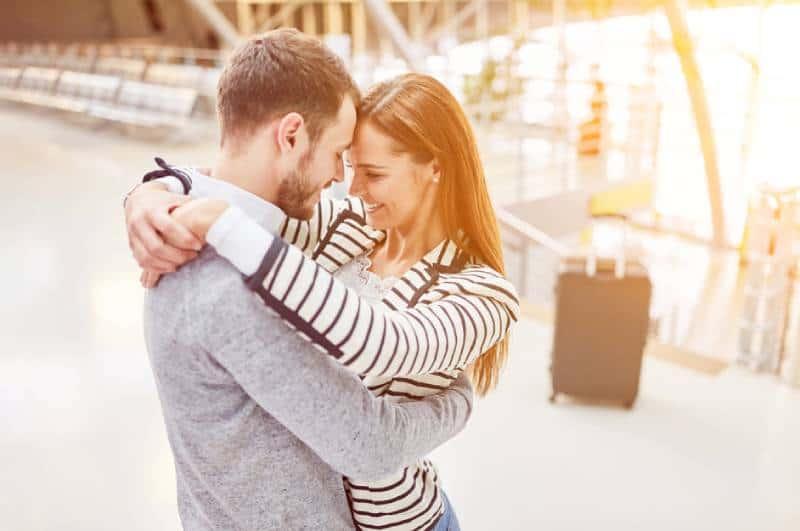 Glückliches Paar umarmt sich am Flughafen
