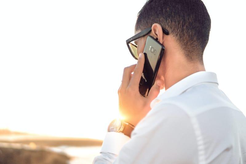 Mann hält Smartphone vor ruhigem Gewässer stehend