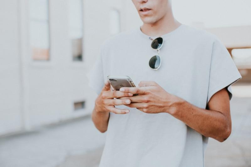 Mann im weißen Top mit Rundhalsausschnitt und Smartphone im Freien