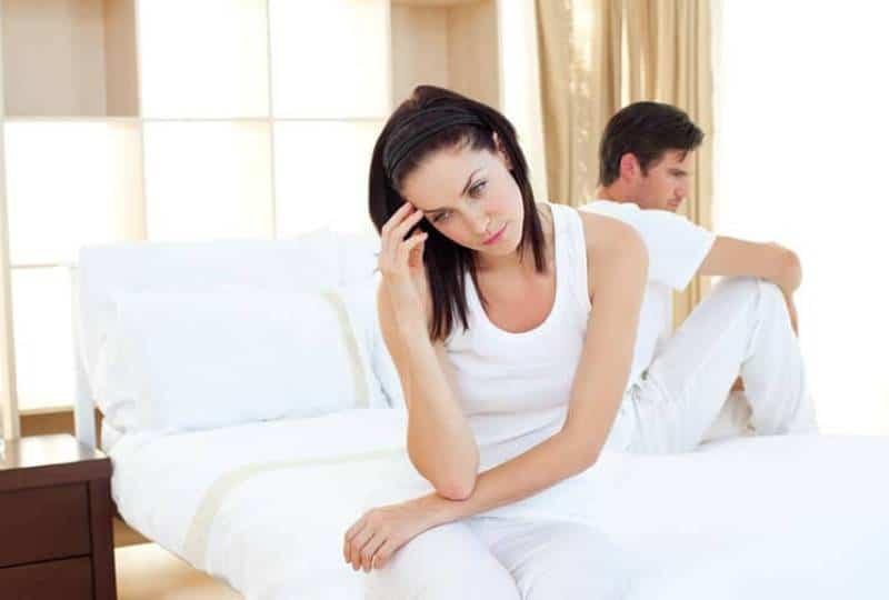Verärgertes Paar, das Ergebnisse eines Schwangerschaftstests im Schlafzimmer herausfindet