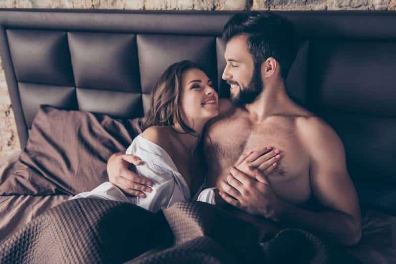 atemberaubende Frau, die ihren Mann im Bett umarmt