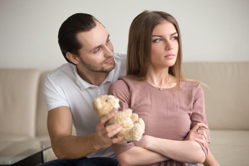 ein Mann, der einer Frau einen Teddybär gibt