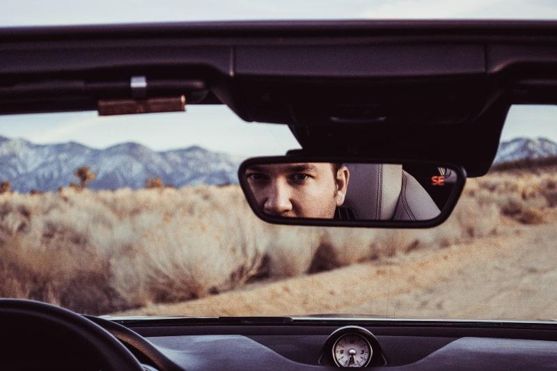 ein Mann, der in den Rückspiegel schaut