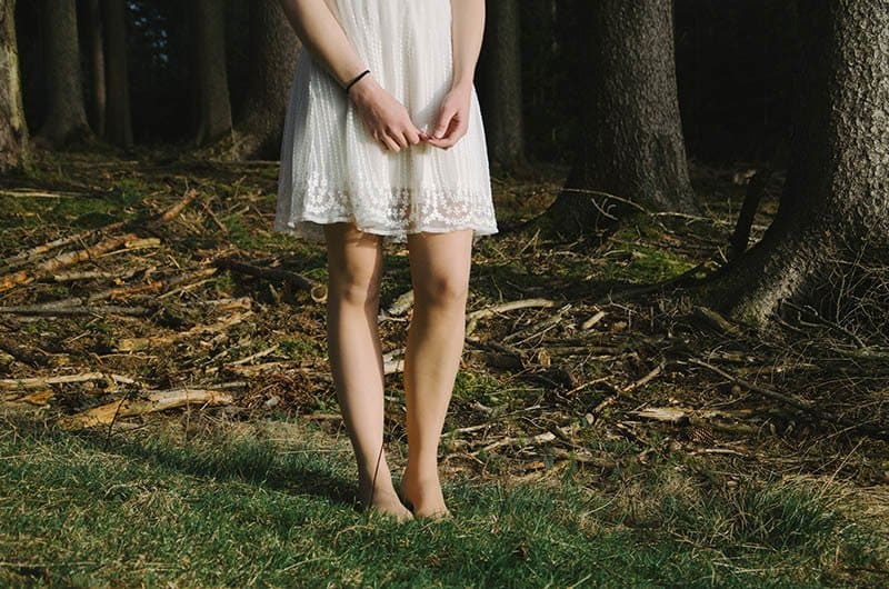 ein barfußes Mädchen in einem weißen Kleid in der Natur