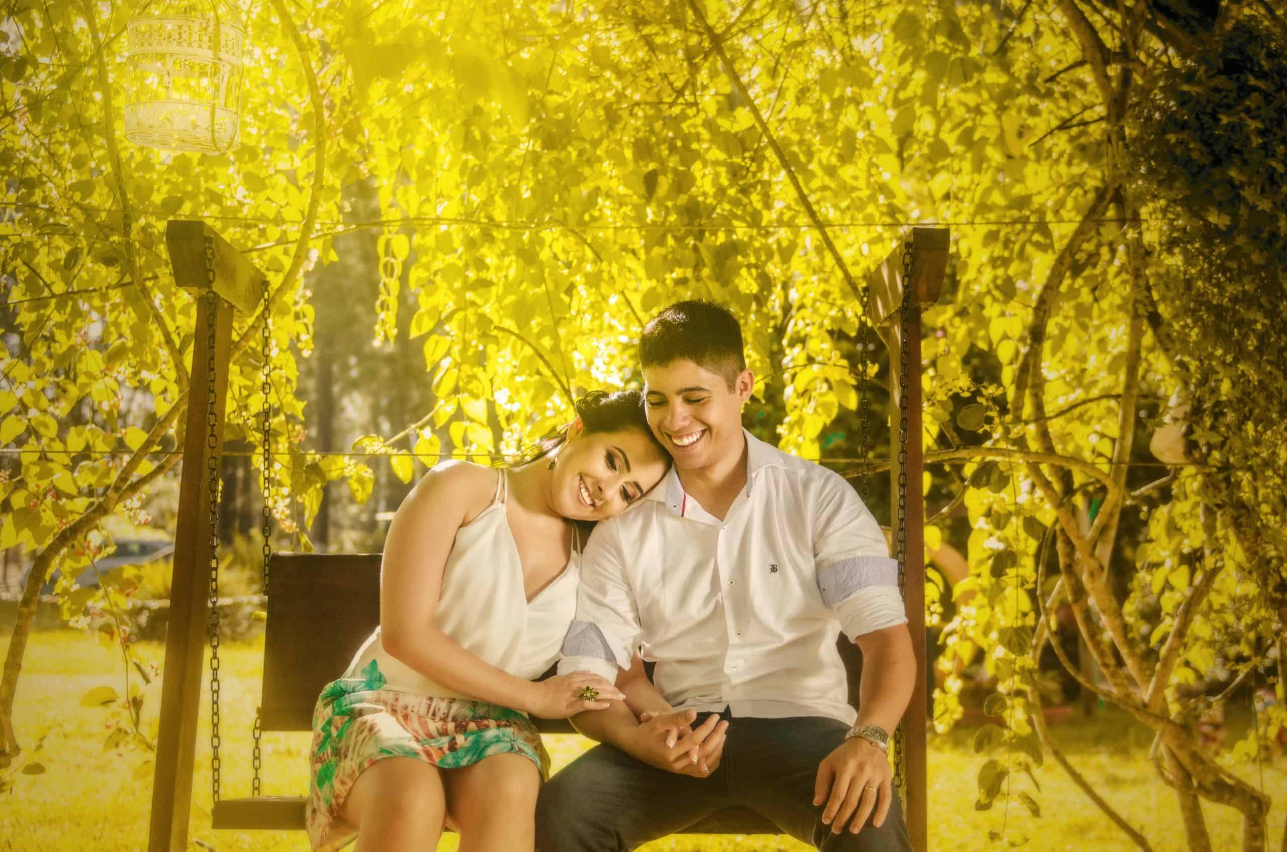 ein lächelndes romantisches Paar sitzt umarmt auf einer Bank