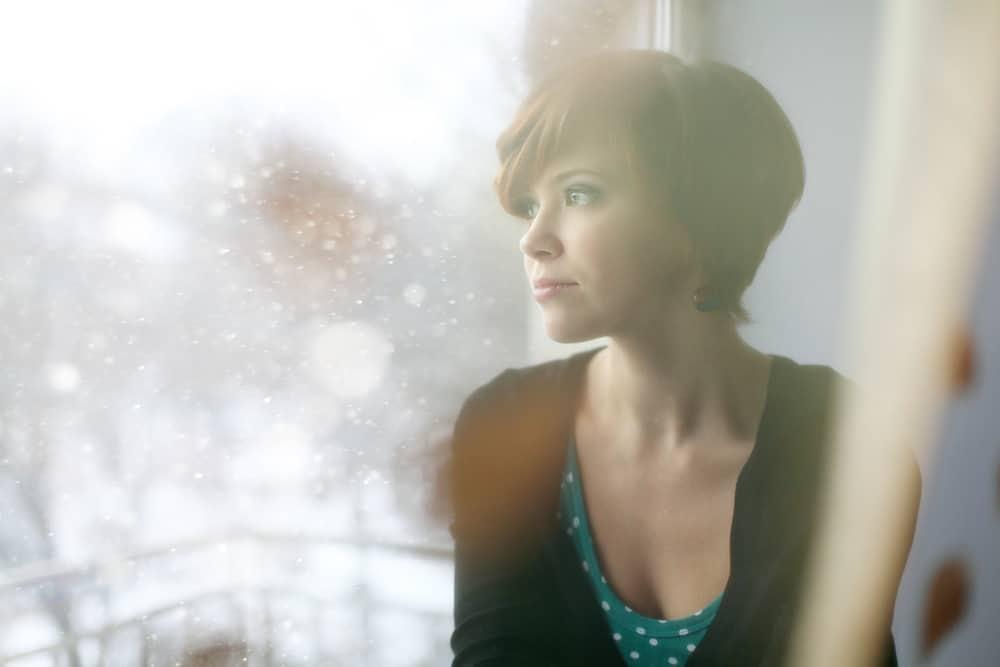 eine besorgte kurzhaarige Frau, die am Fenster sitzt