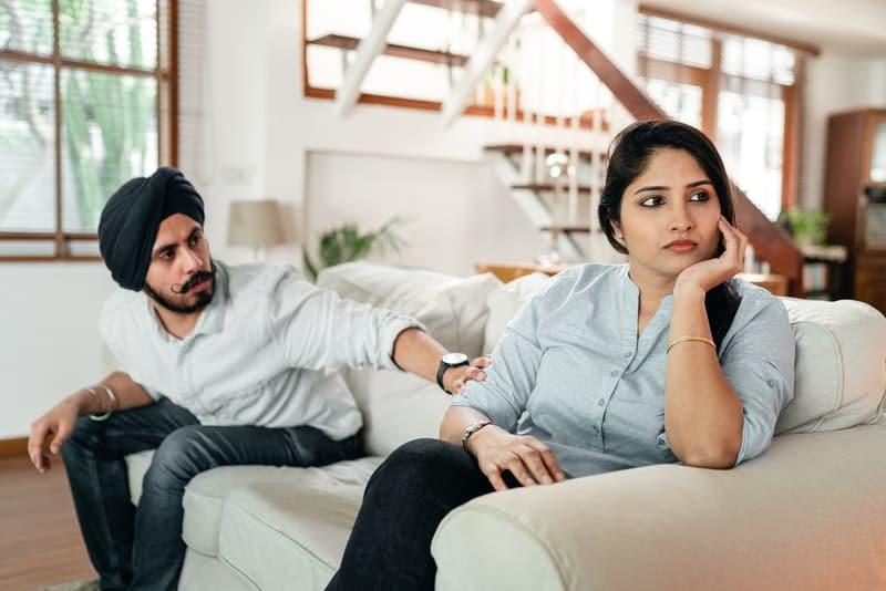 eine nachdenkliche Frau, die mit einem besorgten Mann auf der Couch sitzt