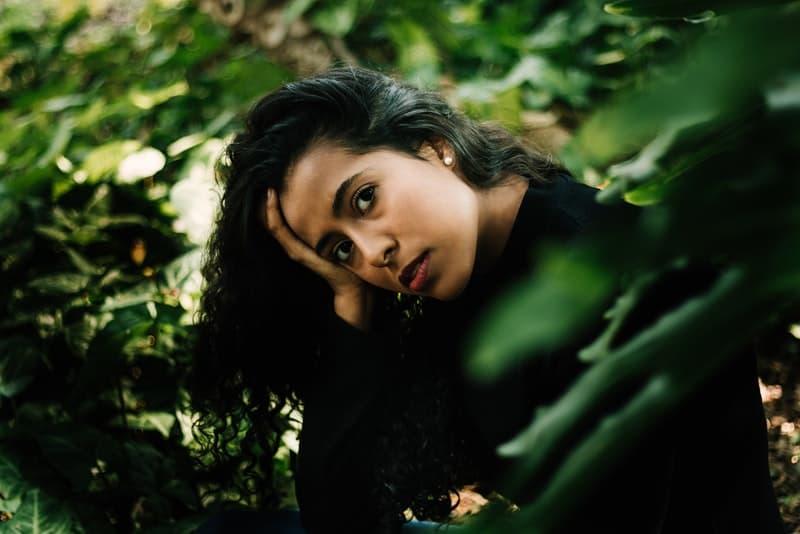 eine verlegene Frau, die im Wald sitzt