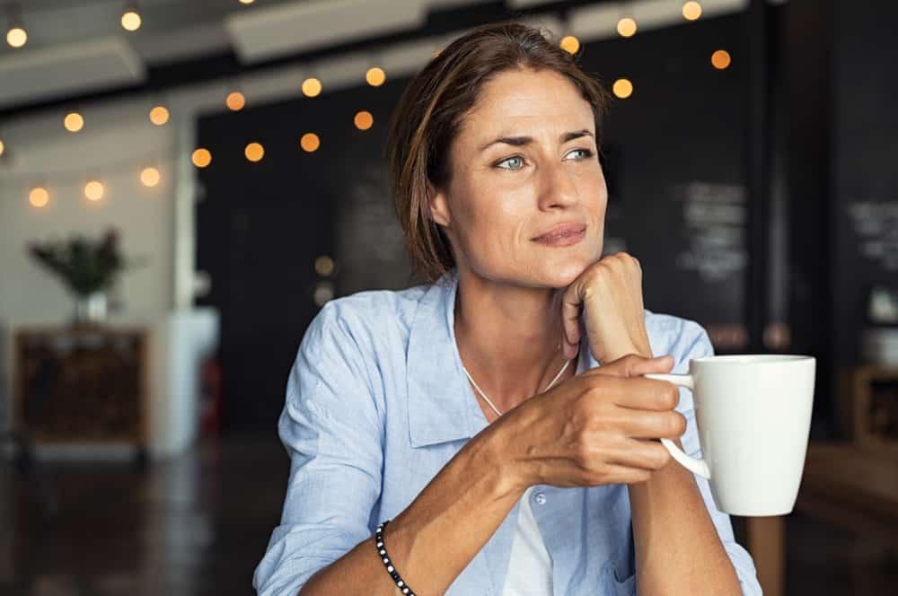 eine zutiefst nachdenkliche Frau, die eine Tasse Kaffee hält