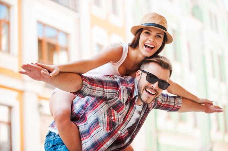 glücklicher Mann huckepack Frau