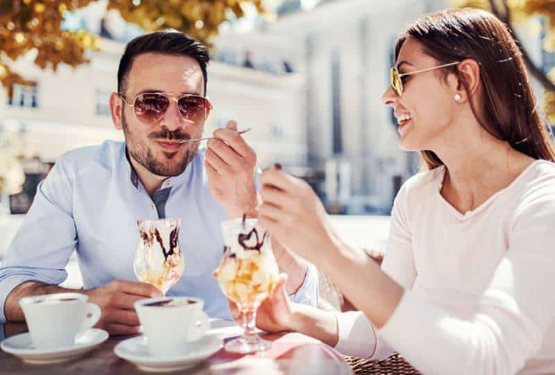 glücklicher Mann und Frau, die Eis im Café essen