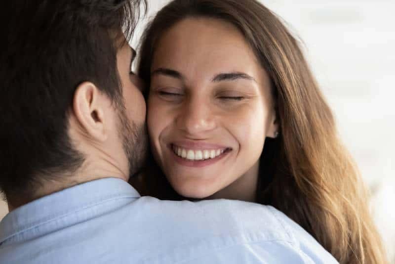 lächelnde Frau, die sich auf die Schulter des Mannes stützt