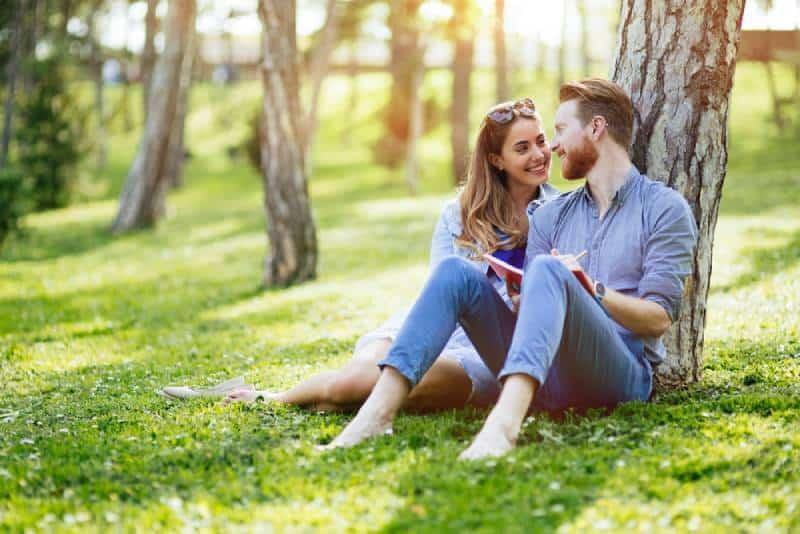 schönes Paar, das auf Gras sitzt und sich auf Baum stützt