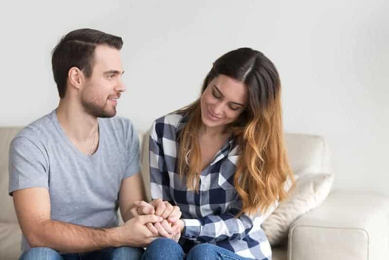 schönes Paar hält Hände zu Hause