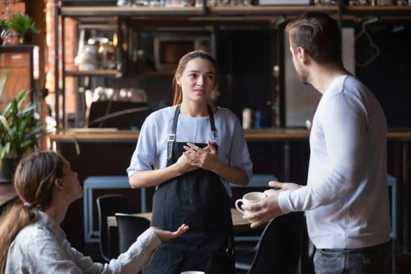 wütendes Restaurant-Kundenpaar im Gespräch mit Kellnern in der Öffentlichkeit