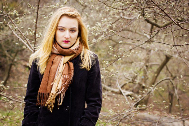 Eine schöne Blondine in einem schwarzen Mantel geht im Frühjahr durch den Park