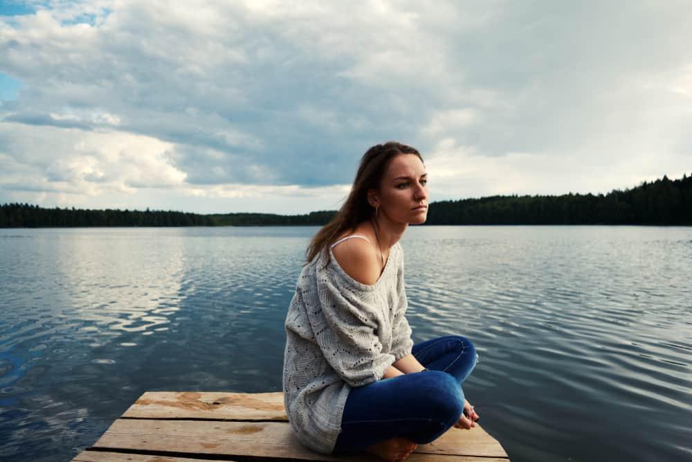 Auf dem Pier des Sees sitzt eine traurige nachdenkliche Frau