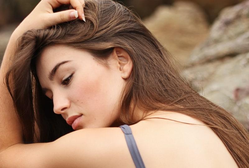 Ein Mädchen im Bikini sitzt auf einem Felsen