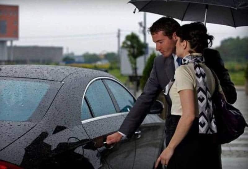 Ein Mann öffnet einer Frau eine Autotür