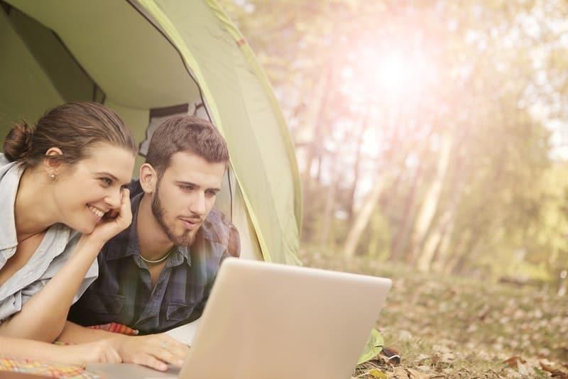 Ein Mann und eine Frau liegen in einem Zelt und beobachten etwas auf einem Laptop