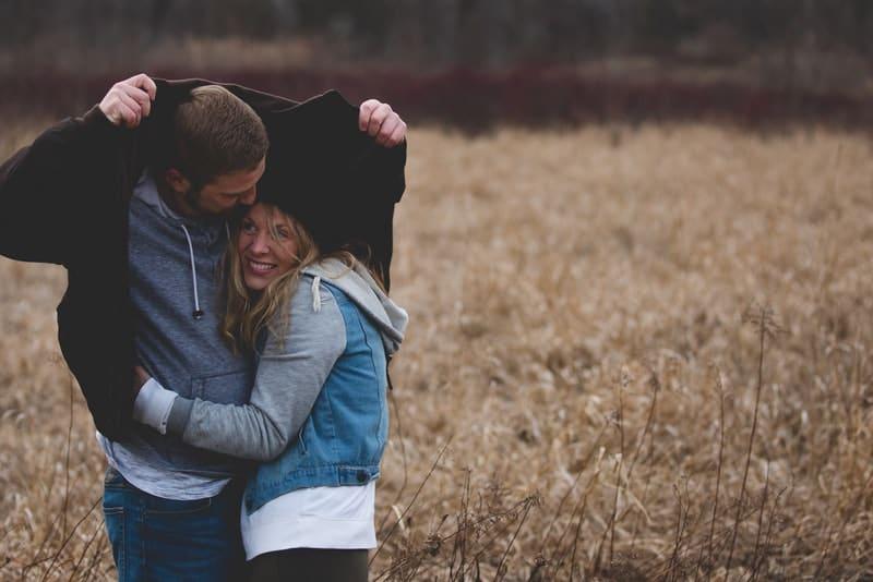 Ein Mann und eine Frau unter einer Lederjacke im Regen