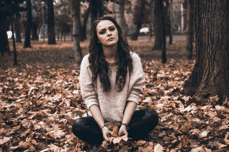Ein trauriges Mädchen sitzt im Wald auf trockenen Blättern