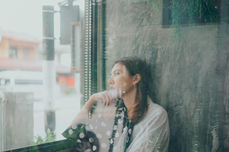 Ein trauriges junges Mädchen sitzt am Fenster, als der Regen fällt