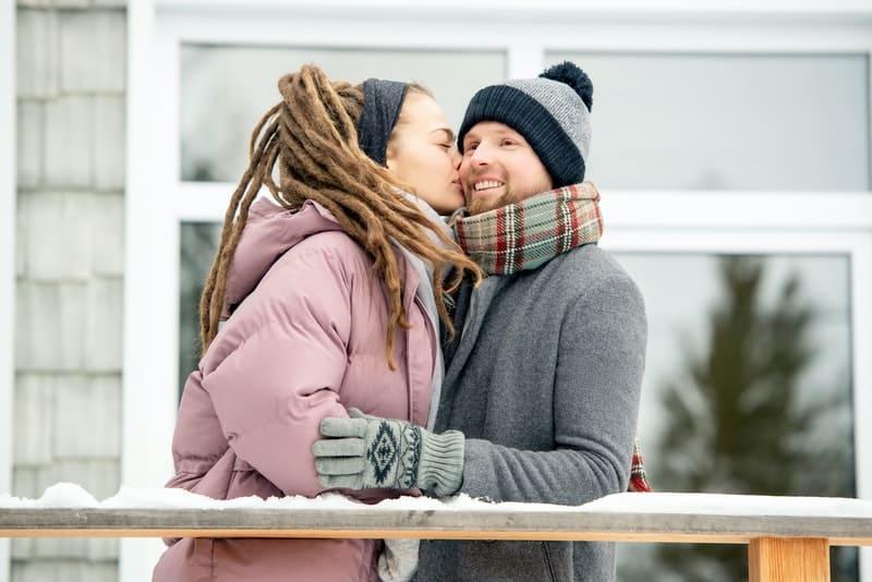 Eine Frau mit Dreadlocks küsst einen Mann auf die Wange