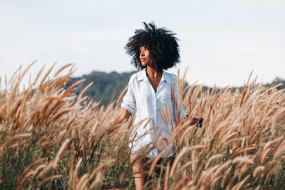 Eine afroamerikanische Frau im Hemd eines Mannes geht durch den Weizen