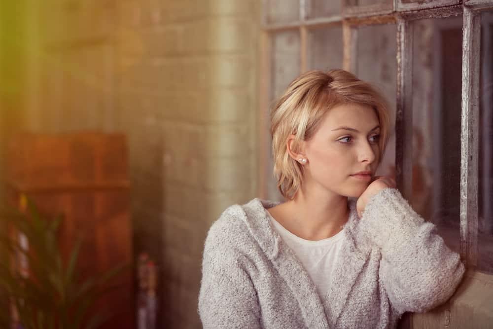 Eine kurzhaarige Blondine steht traurig am Fenster