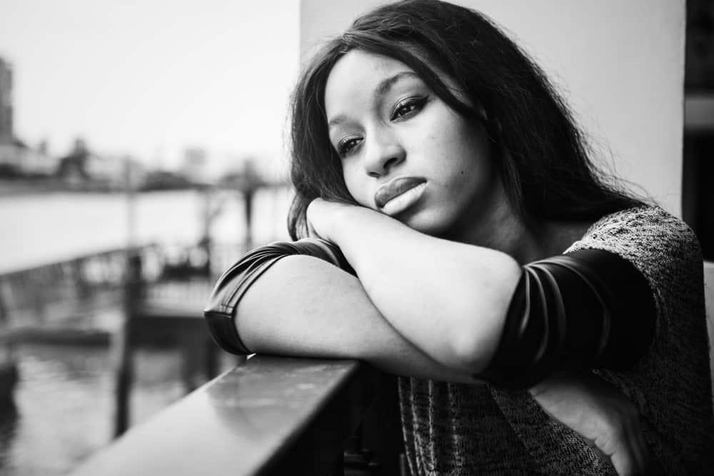Eine traurige Afroamerikanerin sitzt auf dem Balkon