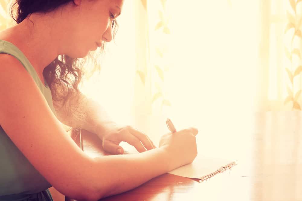 Eine traurige Frau in einem Unterhemd sitzt und schreibt einen Brief