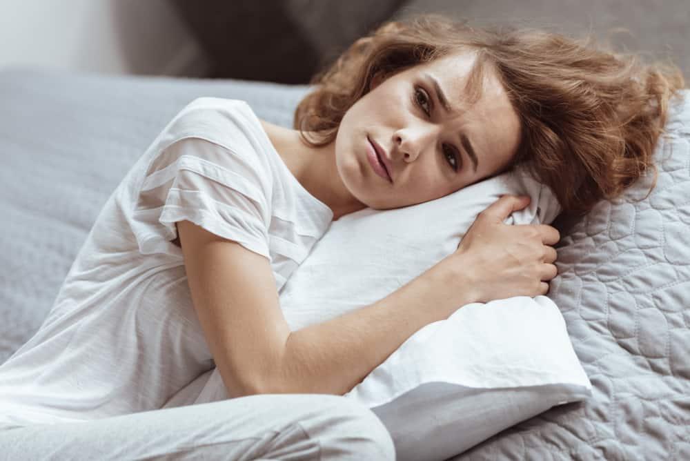 Eine traurige Frau in einem weißen T-Shirt liegt zusammengerollt