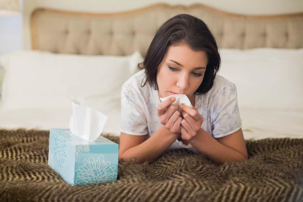 Eine traurige Frau liegt im Bett und wischt sich mit einem Taschentuch die Tränen ab