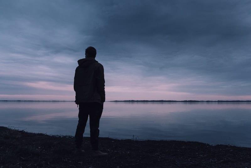 Mann in der Abenddämmerung steht am Strand und beobachtet das Meer