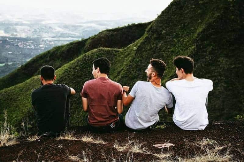 Vier junge Männer sitzen auf einem Berg