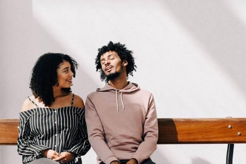 Zwei junge Leute sitzen auf einer Bank und unterhalten sich
