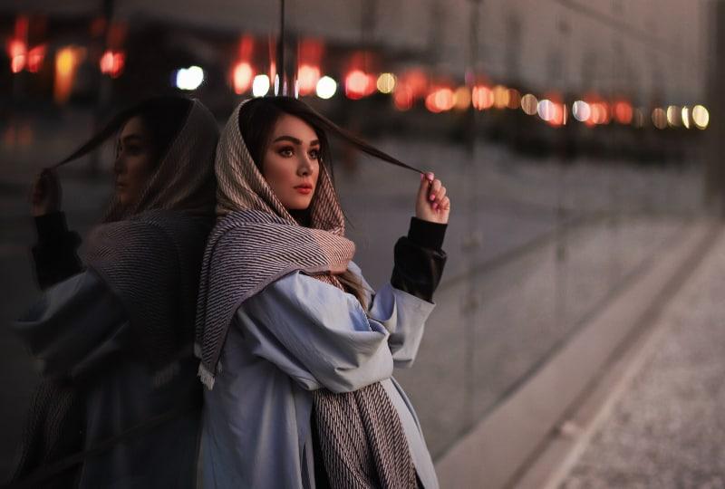 ein Mädchen mit einem Kopftuch, das sich gegen das Glas lehnt